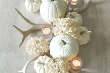 21 a neutral Thanksgiving centerpiece with white antlers, hydrangeas, pumpkins and candles will add a rustic touch to the space