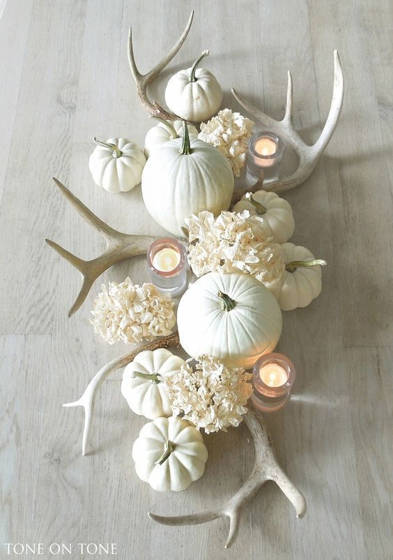 a neutral Thanksgiving centerpiece with white antlers, hydrangeas, pumpkins and candles will add a rustic touch to the space