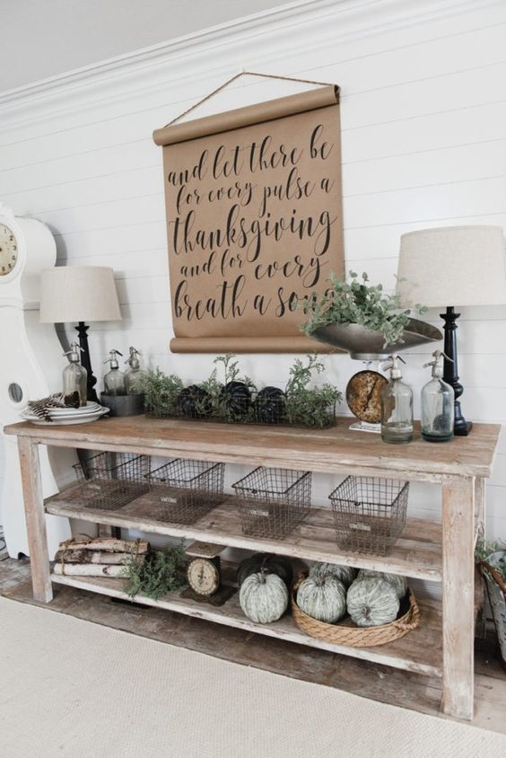 a vintage farmhouse console with heriloom pumpkins, metal wire baskets, foliage and a kraft paper sign over it