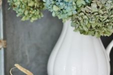 21 a vintage white pitcher with green hydrangeas and pumpkins around is a great decoration or a centerpiece