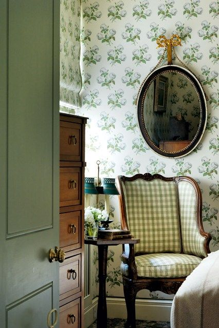 floral print wallpaper and a plaid upholstered chair look harmonious together and are perfect for a cottage