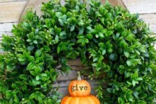 22 a cool and fresh Thanksgiving wreath of boxwood and little pumpkins and a large burlap bow for your front door