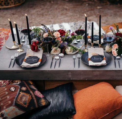 a gorgeous boho chic picnic setting for Halloween with lush florals, candles and black chargers