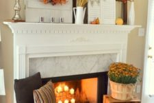 22 a mantel decorated with fall leaves, pumpkins and wheat and a fireplace with candles, pumpkins, fall blooms and lanterns
