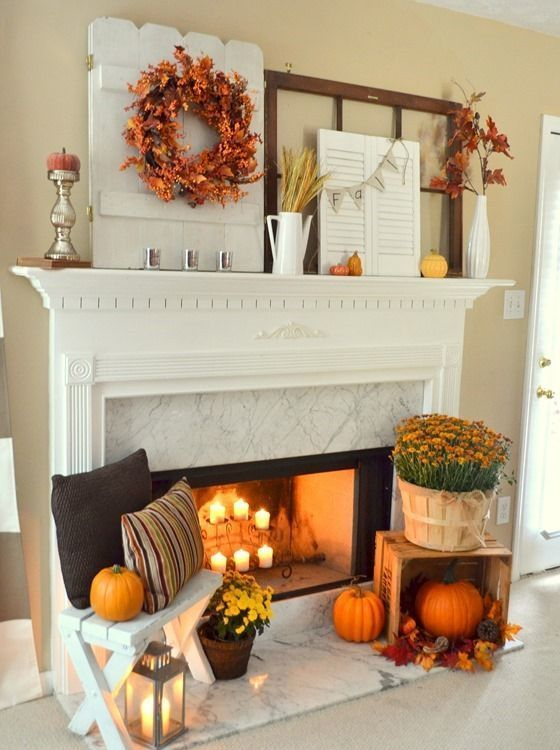 a mantel decorated with fall leaves, pumpkins and wheat and a fireplace with candles, pumpkins, fall blooms and lanterns