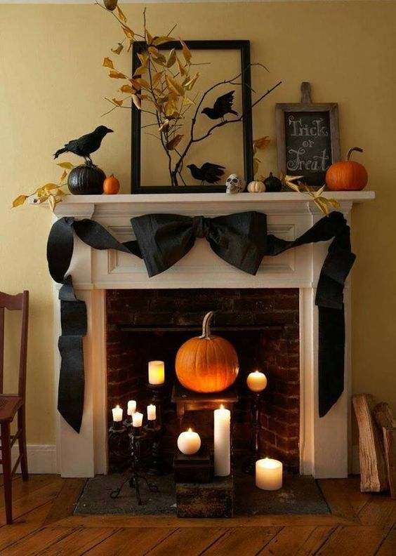a natural fireplace and mantel with a black ribbon bow, fake birds, fall leaves on branches and lots of candles
