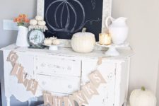 22 a neutral Thanksgiving console with a banner, heirloom pumpkins, little white ones and a jug