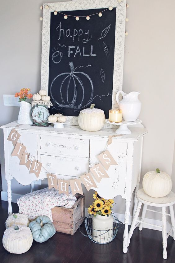 a neutral Thanksgiving console with a banner, heirloom pumpkins, little white ones and a jug