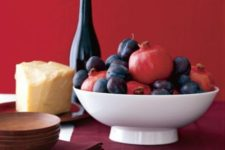 22 a simple bowl centerpiece with pomegranates and plums is a great last-minute idea for Thanksgiving