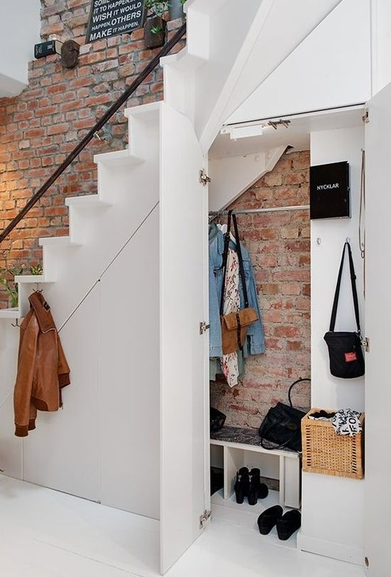 under the stairs space used as a mudroom with enough storage, shelves and holders