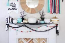 23 a colorful Halloween mantel with bright pompoms, tassels, pumpkins and various garlands