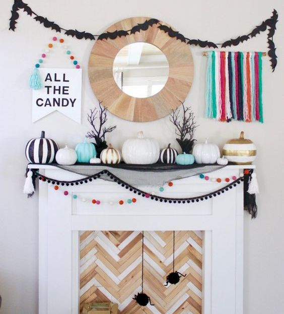 a colorful Halloween mantel with bright pompoms, tassels, pumpkins and various garlands