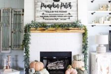 23 a mantel styled with a fresh greenery garland and heirloom pumpkins stacked next to the fireplace
