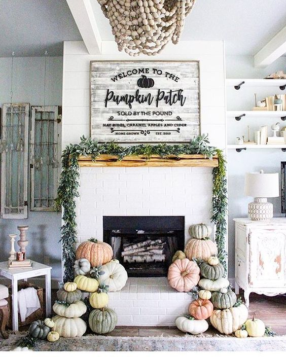 a mantel styled with a fresh greenery garland and heirloom pumpkins stacked next to the fireplace