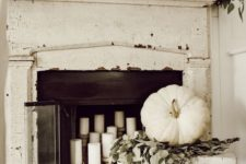 23 a very neutral fall fireplace and mantel, much greenery and white pumpkins and candles