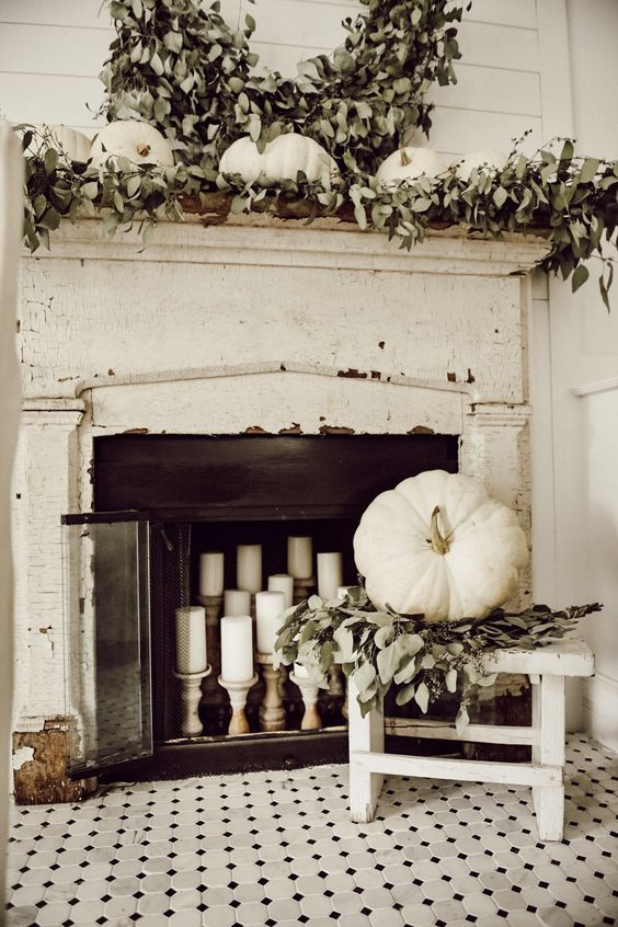 a very neutral fall fireplace and mantel, much greenery and white pumpkins and candles