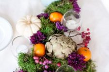 24 a Thanksgiving centerpiece with artichokes, white pumpkins, moss and purple berries and blooms