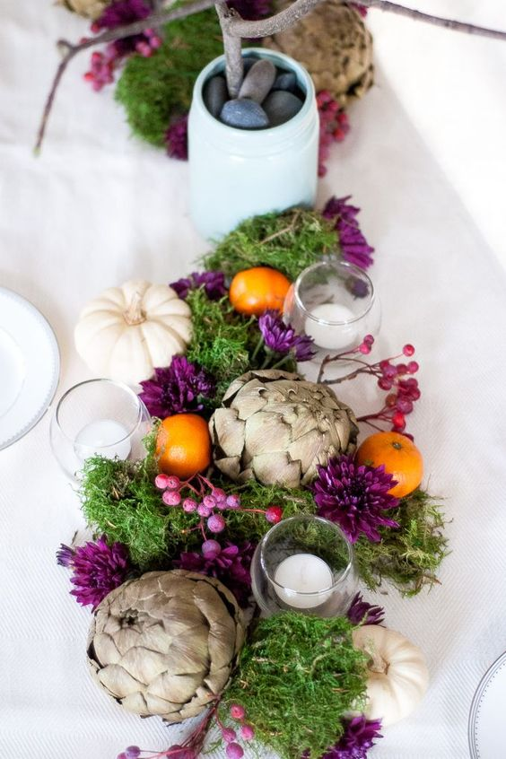 a Thanksgiving centerpiece with artichokes, white pumpkins, moss and purple berries and blooms