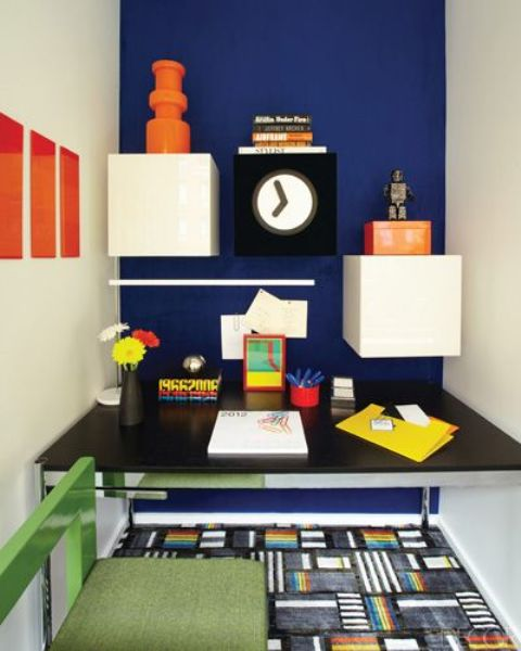a home office nook with a navy wall and white drawers that create a bold color blocking effect