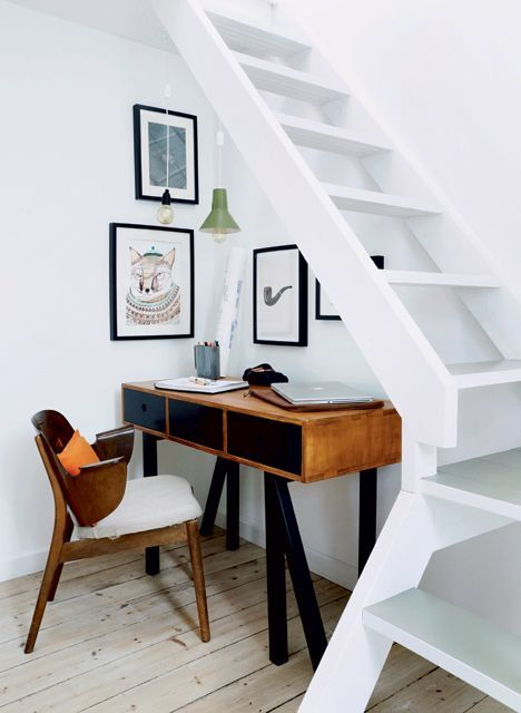 a little and a stylish home office space with mid century modenr furniture and artworks located under the stairs