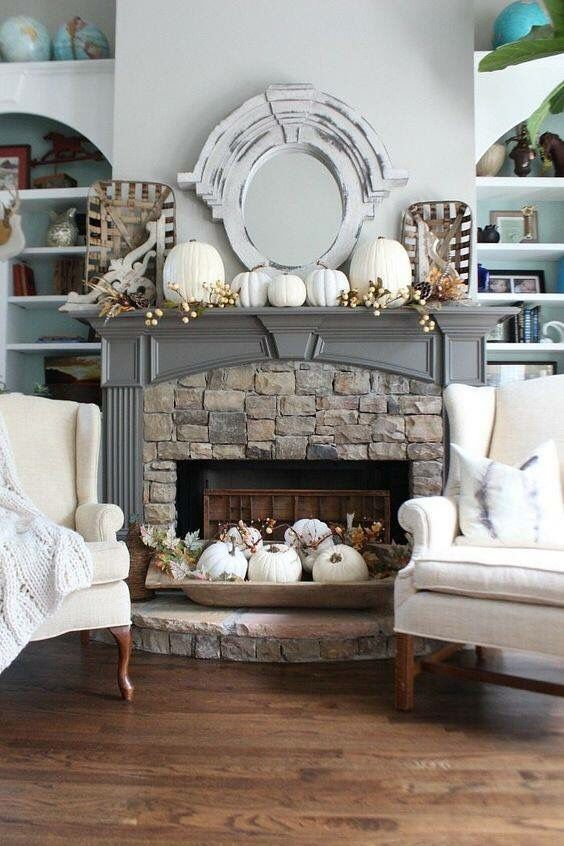a mantel with white pumpkins and berries, a bread bowl with white pumpkins and leaves next to the fireplace