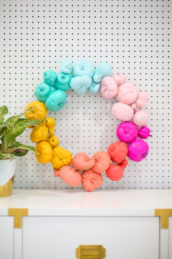 a rainbow pumpkin wreath is a unique take on a traditional Halloween wreath with a spooky feel