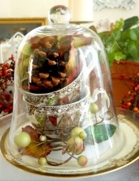 a vintage cloche with a pinecone, vintage cups and fake leaves and apples for a vintage table setting