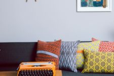 24 abstract pillows on the sofa make it bright and add a mid-century modern feel to it