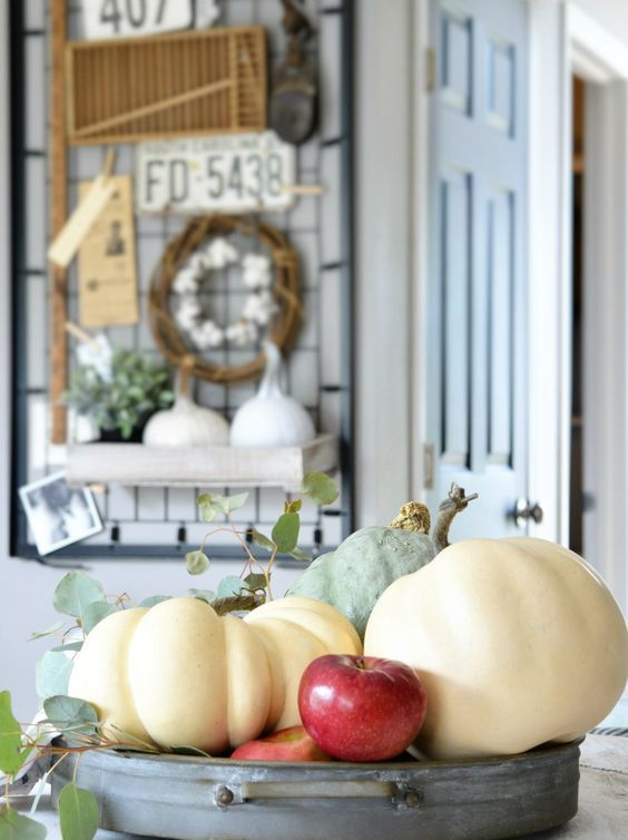 an all natural fall or Thanksgiving centerpiece of a metal bowl, pumpkins, apples and greenery