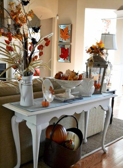 an elegant vintage console with faux  pumpkins, leavesm dried blooms and a metal basket with pumpkins