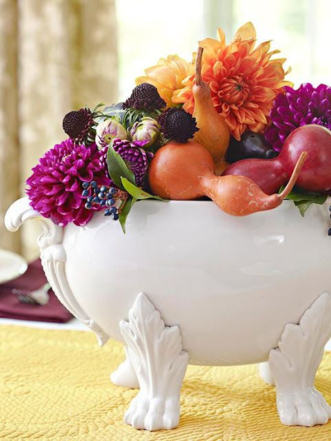 a vintage soup bowl filled with fall fruits and veggies, bright blooms and berries in bright jewel tones