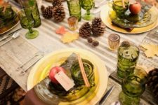 25 an outdoor Thanksgiving tablescape dotted with green glasses and glass plates and foliage and blooms in a birch bark vase