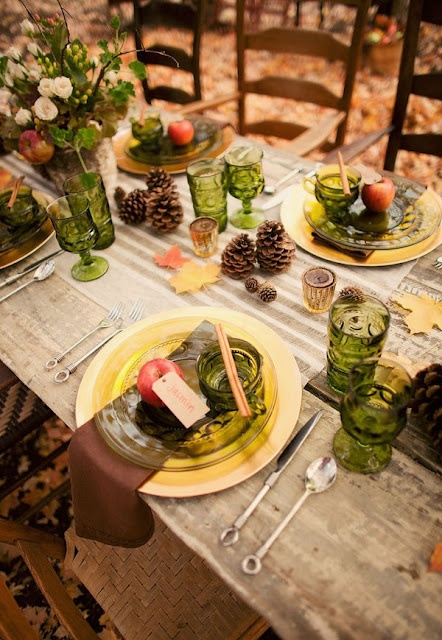 an outdoor Thanksgiving tablescape dotted with green glasses and glass plates and foliage and blooms in a birch bark vase