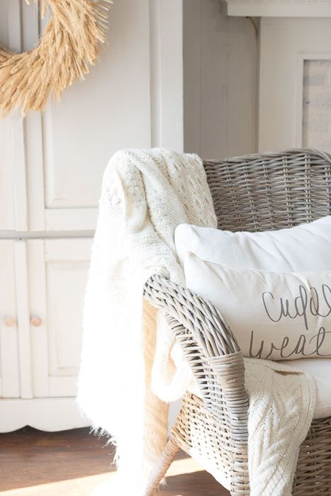 neutral decor with a wheat wreath, a creamy crochet blanket and creamy pillows for fall and Thanksgiving