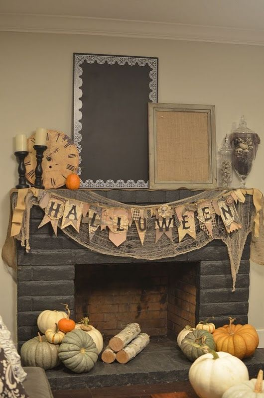rustic and natural Halloween fireplace and mantel with heirloom pumpkins, a banner and some firewood