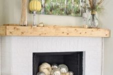 26 simple styling with a birch artwork, feathers, wheat, pumpkins and silver and white pumpkins in the fireplace