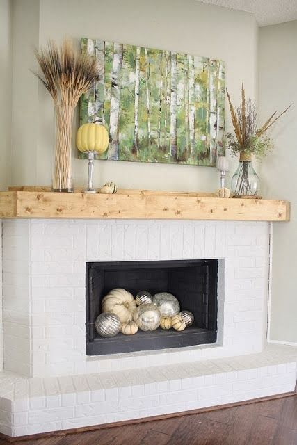 simple styling with a birch artwork, feathers, wheat, pumpkins and silver and white pumpkins in the fireplace