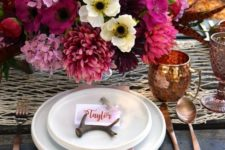 26 the tablescape is influenced by a super lush and bold floral centerpiece in pink, fuchsia and neutrals