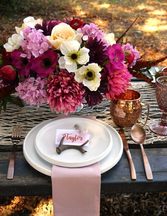 the tablescape is influenced by a super lush and bold floral centerpiece in pink, fuchsia and neutrals