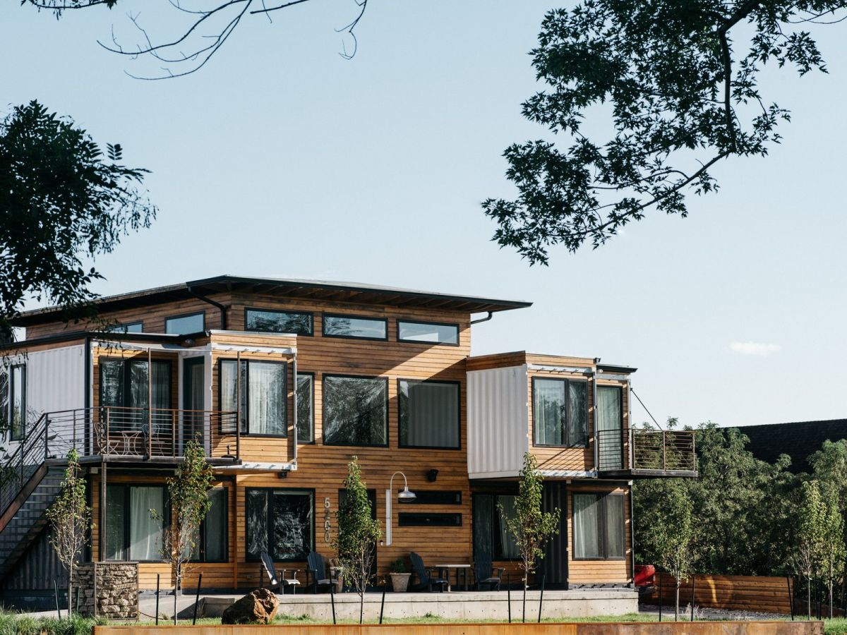 This home is built of shipping containers by its owner for this family, it's clad with wood and metal for a cool rustic look