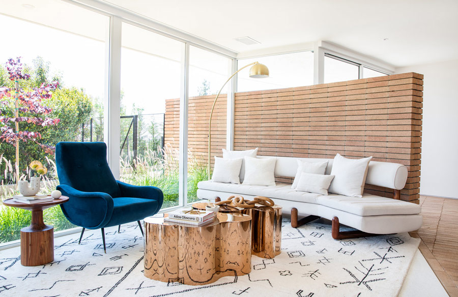 Her'es an outdoor indoor sitting nook with creative coffee tables and comfy mid century modern furniture