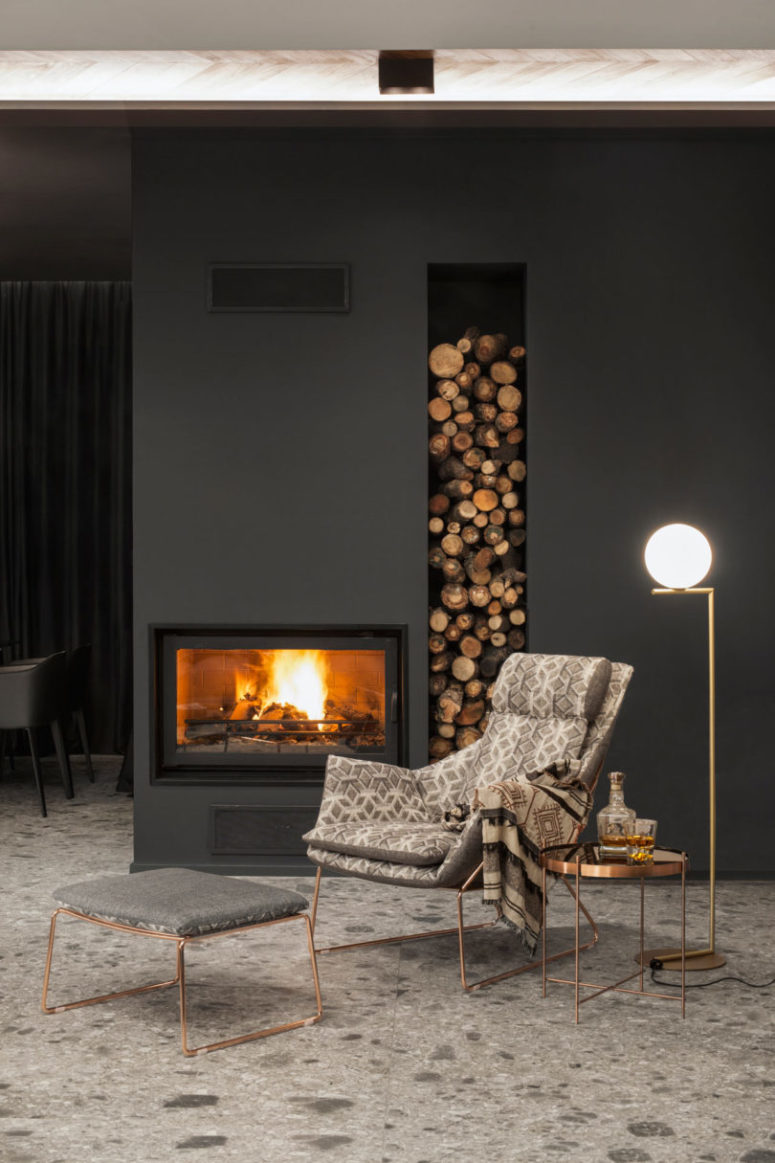 Stone, graphite and black surfaces were softened with wood and warm metals - copper and gold plus a firewood storage unit like here