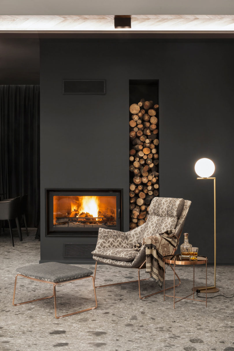 Stone, graphite and black surfaces were softened with wood and warm metals   copper and gold plus a firewood storage unit like here