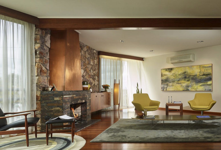 The living room features a large fireplace clad with stone and copper, lemon yellow chairs and a matching artwork plus colorful rugs that cozy up the space