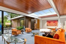 02 The living room features bold orange furniture, catchy glass tables, an entrance to an outdoor space and a large skylight
