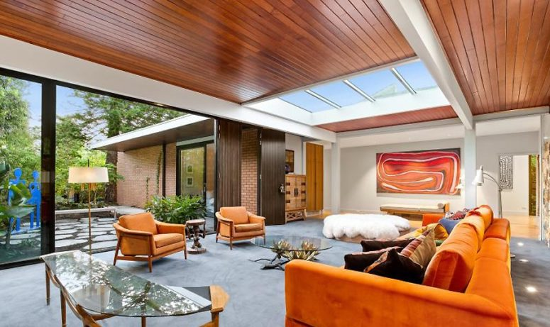 The living room features bold orange furniture, catchy glass tables, an entrance to an outdoor space and a large skylight