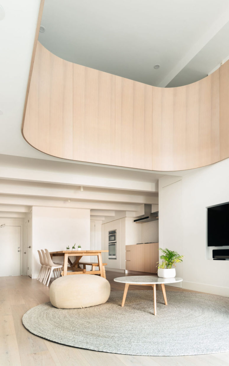 The main space is an open layout of a kitchen, dining space and a living room, filled with light and air
