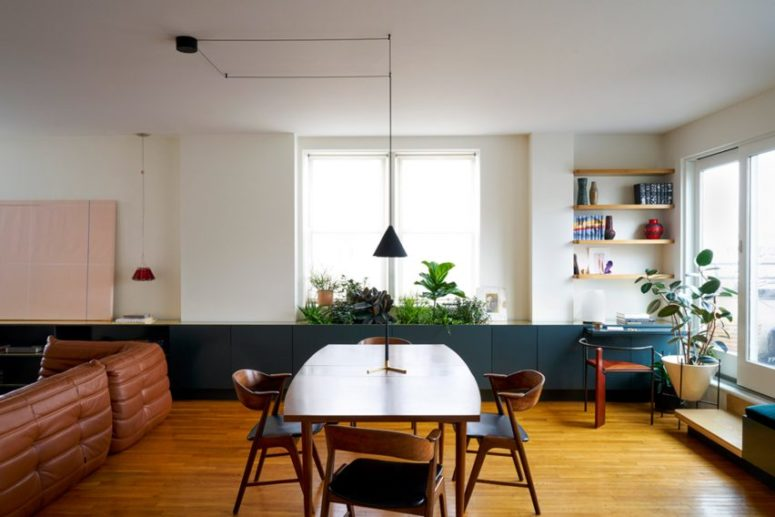 The main space was an open layout with a living and dining space, and a kitchen, too. There is a long row of cabinets in forest green for storage