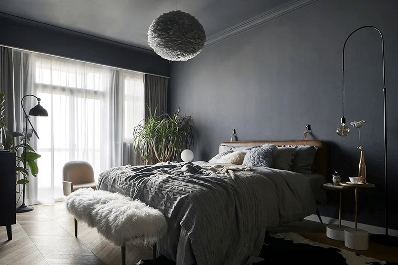The master bedroom is grey, with a leather upholstered bed, a faux fur bench, some comfy furniture and a fluffy cloud lamp over it all