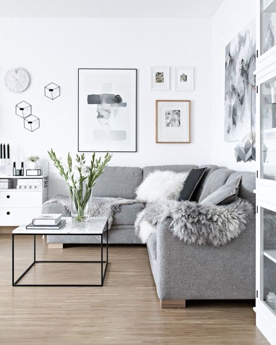 a Scandinavian living room done in white and greys, faux fur and pillows add coziness to the space